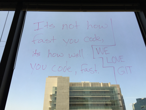 """whiteboard marker writing on the inside of a skyscraper window with the quote """"It's not how fast you code, it's how well you code, fast"""" and """"We love Git"""""""